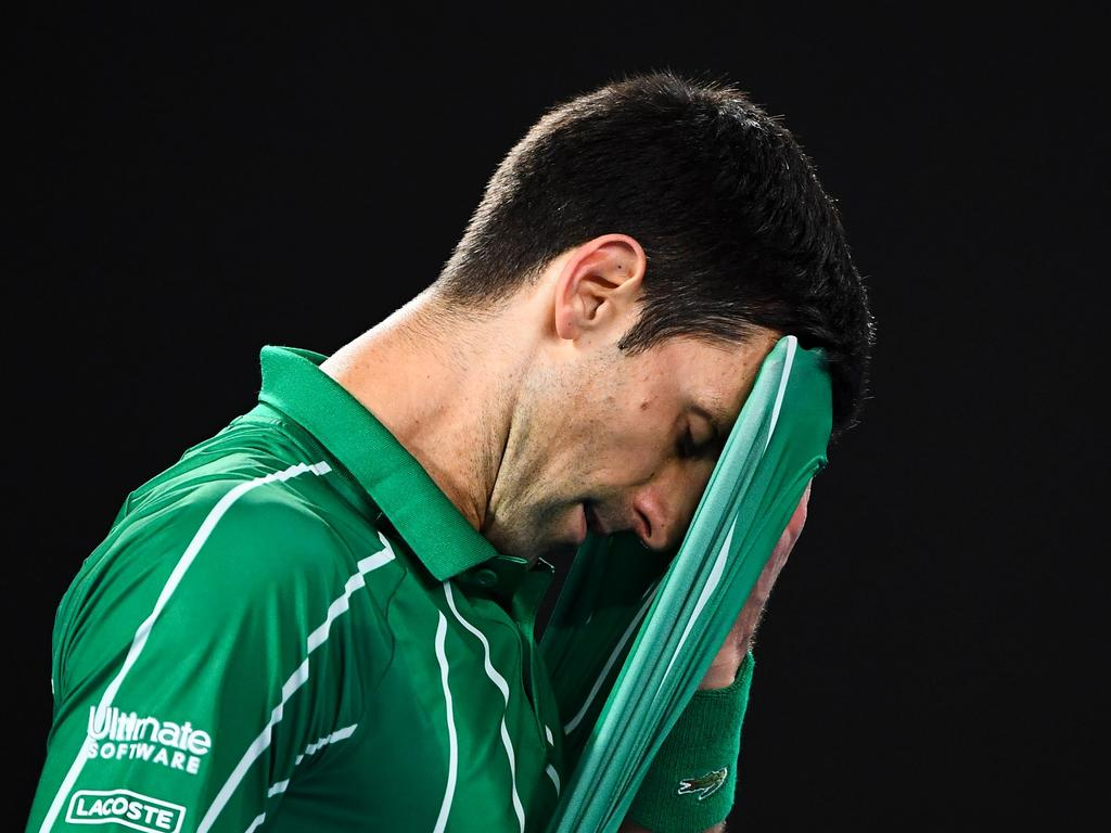Serbia's Novak Djokovic reacts after a point against Austria's Dominic Thiem during their men's singles final match on day fourteen of the Australian Open tennis tournament in Melbourne on February 2, 2020. (Photo by William WEST / AFP) / IMAGE RESTRICTED TO EDITORIAL USE - STRICTLY NO COMMERCIAL USE