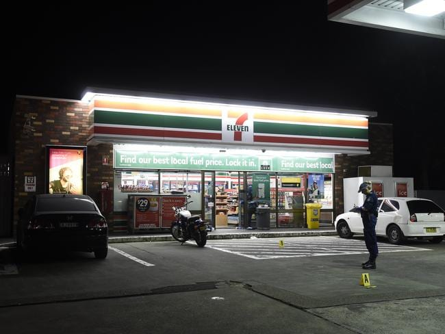 An officer takes notes outside the Enmore 7-Eleven in the aftermath of the axe attack which took place at 2.20am last Saturday. Picture: Gordon McComiskie