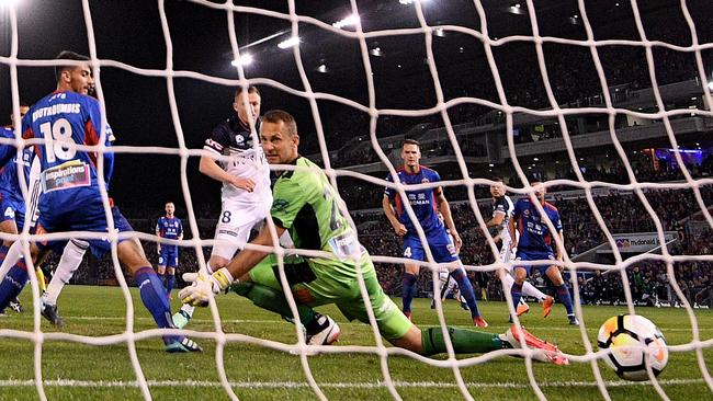 Newcastle Jets goalkeeper Glen Moss watches as the ball goes in the net for Melbourne Victory's goal.