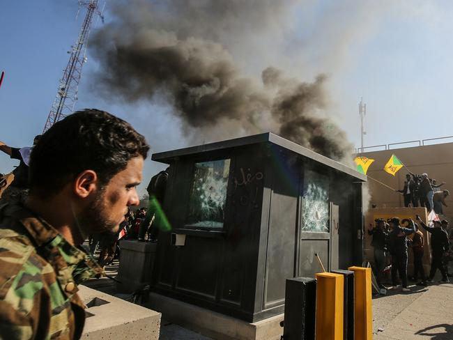 Members of the Iraqi pro-Iranian Hashed al-Shaabi group and protesters set ablaze a sentry box in front of the US embassy building in the capital Baghdad. Picture: AFP