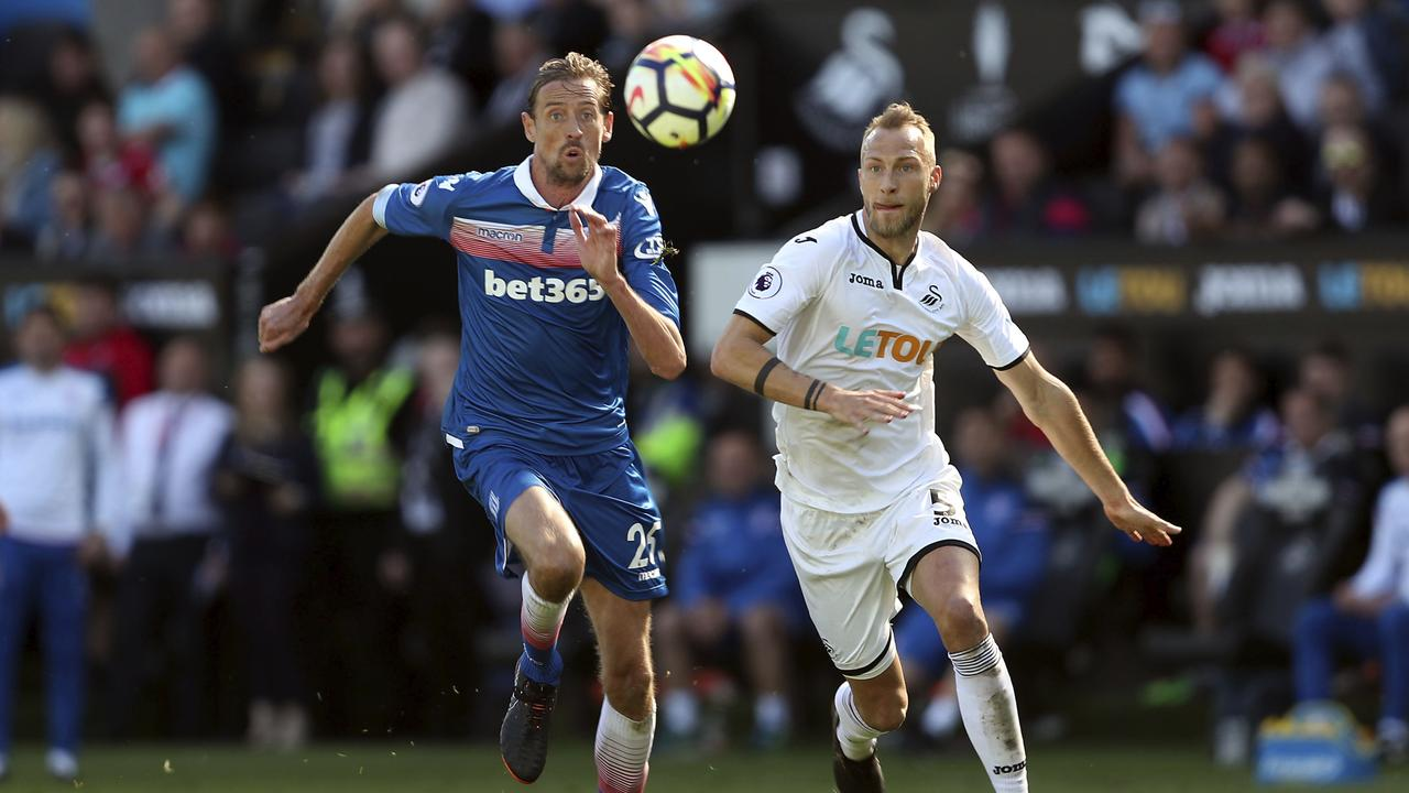 Stoke City's Peter Crouch, left and Swansea City's Mike van der Hoorn battle for the ball