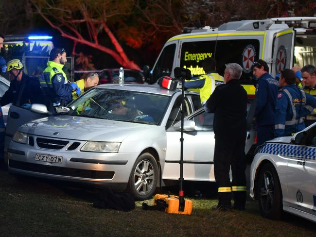 Ambulance paramedics, a Careflight crew and police treat a man sitting in a car with a speargun spear in his chest. Picture: Sebastien Dekker