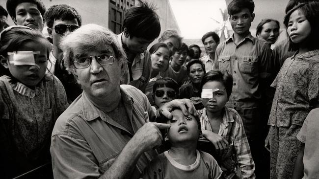 Professor Fred Hollows examines the eye of Tran Van Giap in the courtyard of Hanoi Institute of Ophthalmology in 1992. The portrait of Fred and Giap, who was eight at the time, has become the iconic image of The Fred Hollows Foundation. Picture: Michael Amendolia