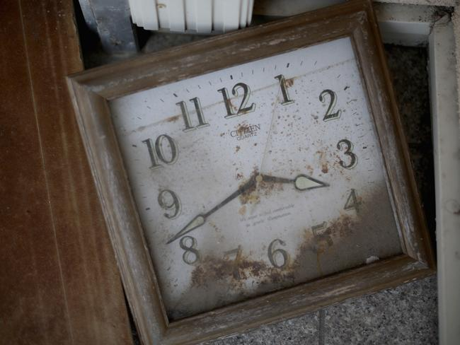 A stopped clock covered in five years of dust, sits in a tsunami damaged home inside the exclusion zone close to the devastated Fukushima nuclear plant. Picture: Getty