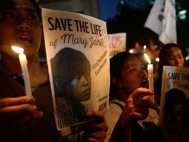 Vigils ... Activists holding candles and portraits of Filipina Mary Jane Veloso. Picture: AFP