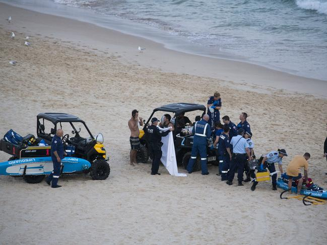 A young male being assisted by emergency services after he almost drowned after being caught in a notorious rip at the southern end of Bondi Beach. Picture: Dylan Robinson