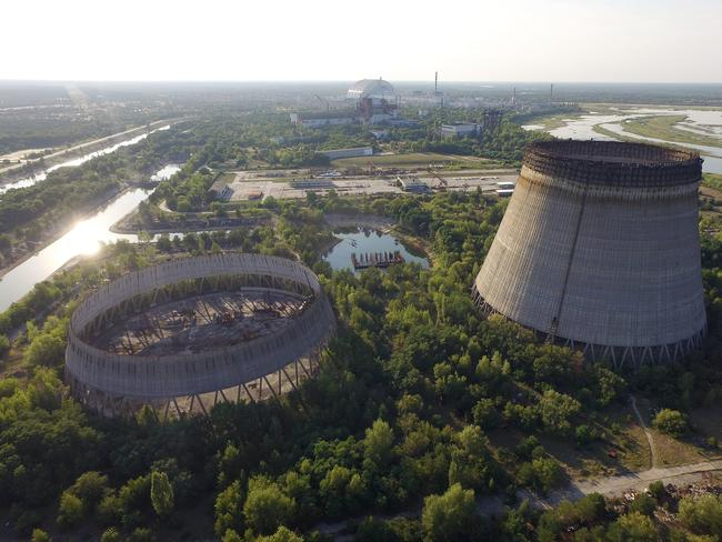 In this aerial view abandoned, partially-completed cooling towers stand at the Chernobyl nuclear power plant as the new, giant enclosure that covers devastated reactor number four stands behind in 2017. Picture: Getty