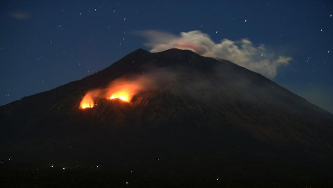 Trees burn on the slopes of Mount Agung as bright orange lava cascades from its summit. Picture: AFP PHOTO / SONNY TUMBELAKA