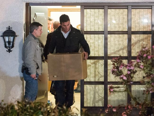 Search ... police carry computer, a box and bags out of the residence of the parents of Andreas Lubitz. Picture: Thomas Lohnes/Getty Images