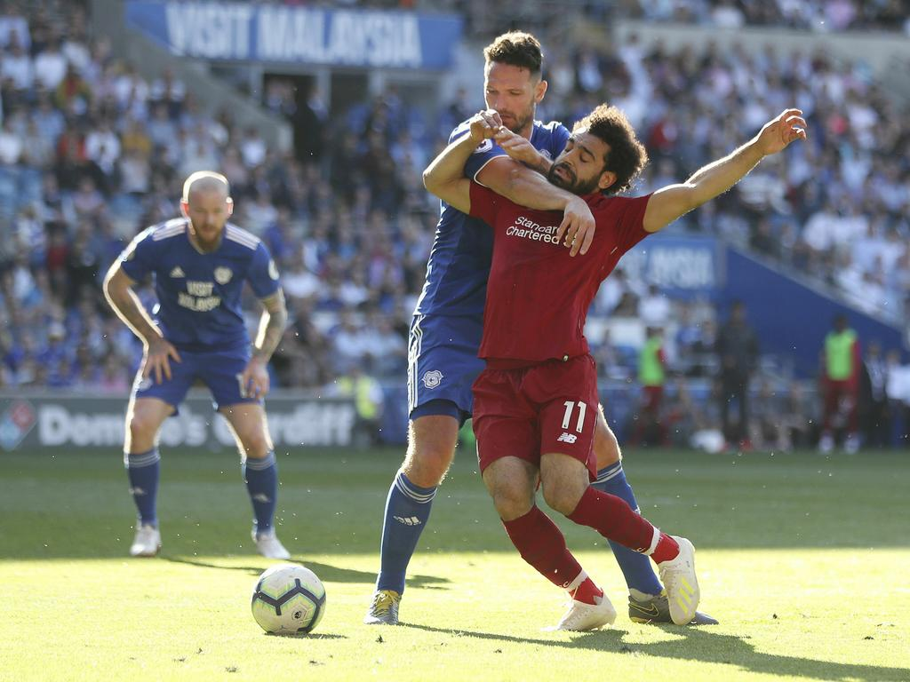 Liverpool's Mohamed Salah, front, is fouled by Cardiff City's Sean Morrison and wins a penalty during the English Premier League soccer match at The Cardiff City Stadium, Cardiff, Wales, Sunday April 21, 2019. (David Davies/PA via AP)