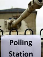 A polling station sign is pictured on a fence enclosing a 2S3 M-1973 Akatsiya 152-mm self-propelled gun howitzer, standing outside the Greenwich Heritage Centre, set up as a polling station, in London on June 23, 2016, as Britain holds a referendum to vote on whether to remain in, or to leave the European Union (EU). Millions of Britons began voting Thursday in a bitterly-fought, knife-edge referendum that could tear up the island nation's EU membership and spark the greatest emergency of the bloc's 60-year history. / AFP PHOTO / DANIEL SORABJI