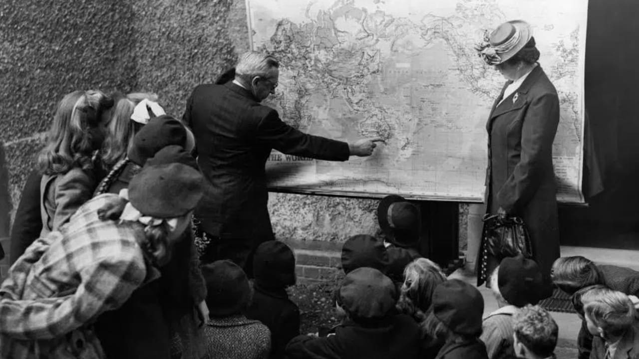 British children looking at a map of Australia where the boys will go to a farming school and the girls to a domestic service training home.