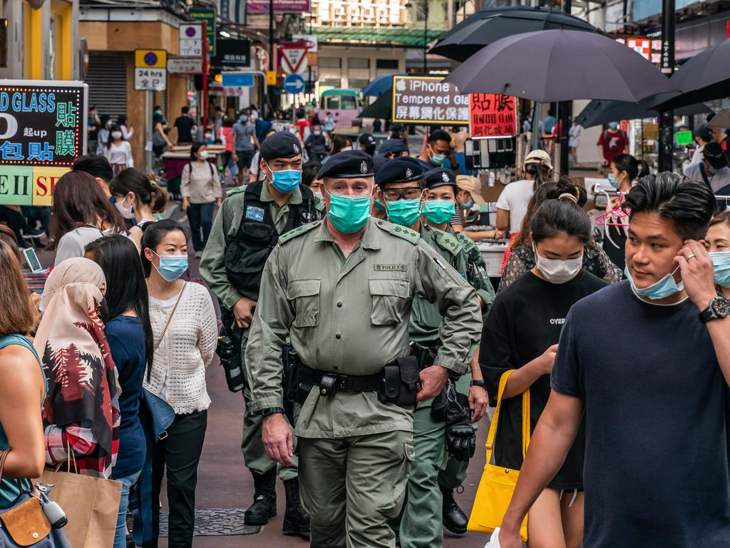 Riot police walk among a Hong Kong shopping district. Picture: Getty Images