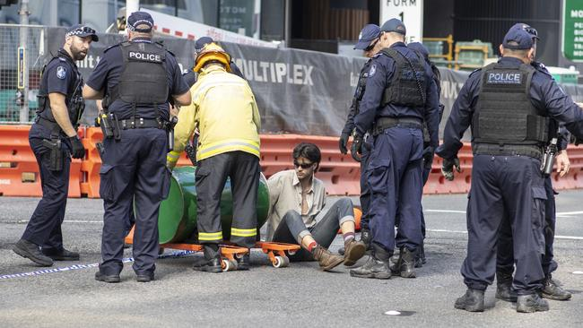 An activist from Extinction Rebellion with his arm in a barrel of cement blocks an intersection in Brisbane. Picture: AAP