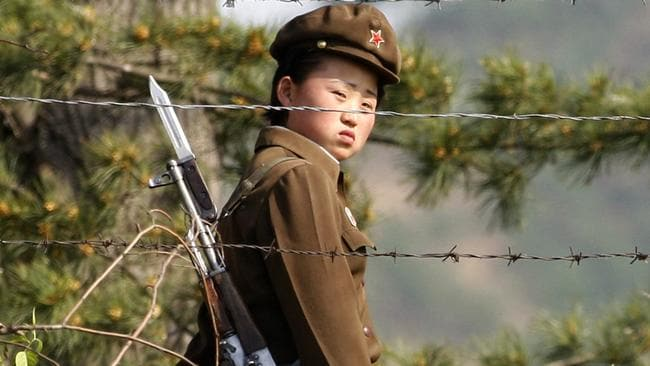 A North Korean soldier looks out from behind a barbed-wire fence around a camp on the North Korean river banks across from Hekou in China's Liaoning province.
