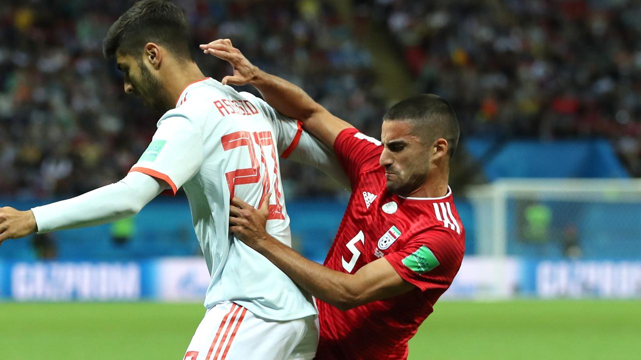 28be29ee0e8 Milad Mohammadi of Iran tackles Marco Asensio of Spain.