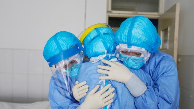 Medical staff members hugging each other in an isolation ward at a hospital in Zouping in China's easter Shandong province. Picture: STR/AFP