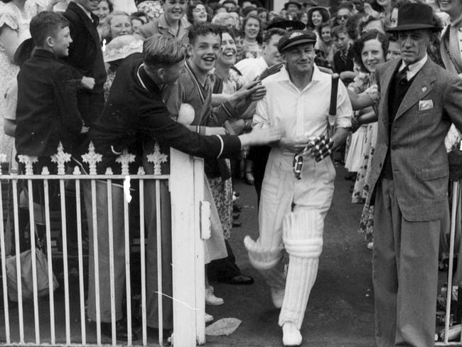 Retired Australian captain Don (later Sir Donald) Bradman walking out to bat at his testimonial match at the MCG in Melbourne in 1948.