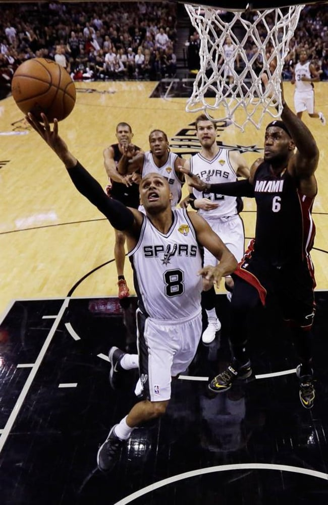 Patty Mills #8 of the San Antonio Spurs goes to the basket against LeBron James.