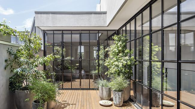 Walls of windows frame a leafy deck at the property.