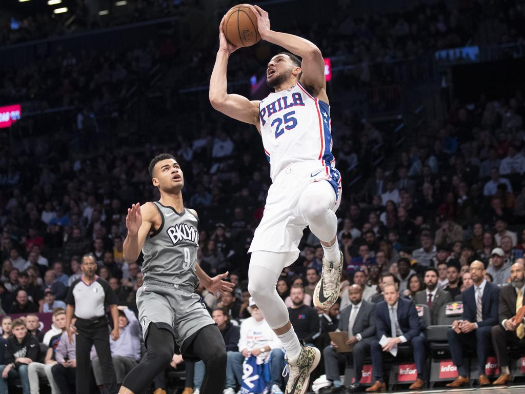 Ben Simmons goes to the basket past Brooklyn Nets guard Chris Chiozza.