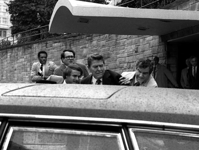 US President Ronald Reagan, centre, is shoved into the President's limousine by secret service agents after being shot outside a Washington hotel on March 30, 1981. Picture: Ron Edmonds.