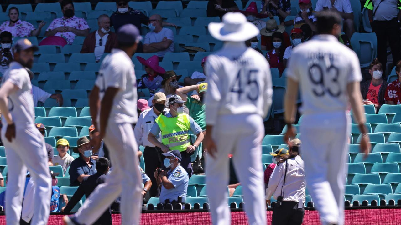 A policeman (C) stands guard among sections of the crowd as the game was halted after allegedly some remarks were made by the spectators on the fourth day of the third Test. (Photo by DAVID GRAY / AFP)