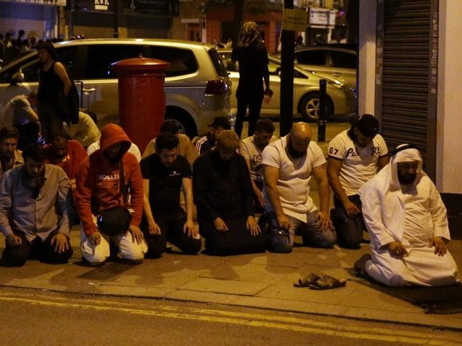 Muslims pray on a sidewalk near a mosque in north London after a vehicle mowed down pedestrians. Picture: AFP Photo/Daniel Leal-Olivas