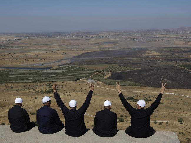 Men of the Druze faith at the Israeli-annexed Golan Heights flash the V for victory sign as they look out across southwestern Syria. Picture: AFP
