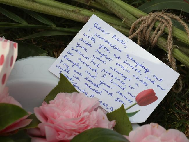A message is left on a flower tribute at Princes Park. Picture: David Crosling/AAP