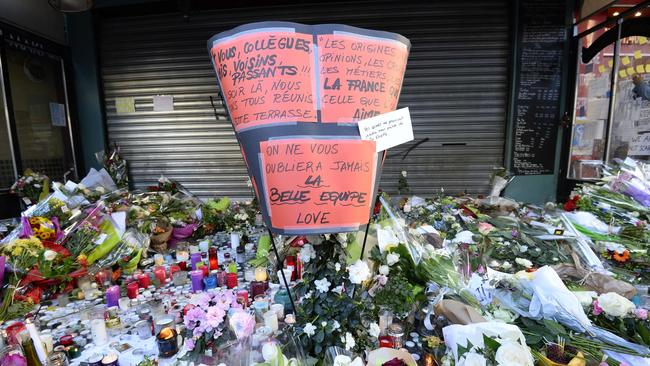 In memory ... Flowers, candles and messages are left as part of a memorial outside La Belle Equipe bar. Picture: Betrand Guay