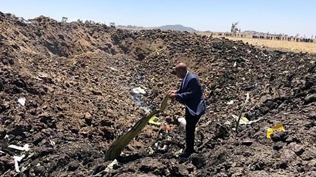 A man inspecting what is believed to be wreckage at the crash site of an Ethiopia Airlines aircraft near Bishoftu, a town some 60km southeast of Addis Ababa, Ethiopia.