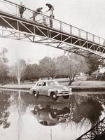Uni students hang an FJ Holden from the Adelaide University footbridge, as a Prosh Week prank in 1971.