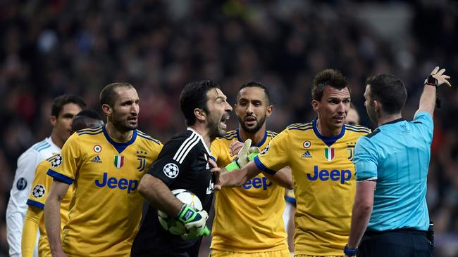 Juventus' Italian goalkeeper Gianluigi Buffon (2L) argues with the referee