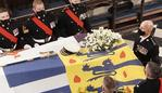 WINDSOR, ENGLAND - APRIL 17: Queen Elizabeth II (left) watches as pall bearers place the coffin of the Duke of Edinburgh during his funeral in St George's Chapel at Windsor Castle on April 17, 2021 in Windsor, England. Prince Philip of Greece and Denmark was born 10 June 1921, in Greece. He served in the British Royal Navy and fought in WWII. He married the then Princess Elizabeth on 20 November 1947 and was created Duke of Edinburgh, Earl of Merioneth, and Baron Greenwich by King VI. He served as Prince Consort to Queen Elizabeth II until his death on April 9 2021, months short of his 100th birthday. His funeral takes place today at Windsor Castle with only 30 guests invited due to Coronavirus pandemic restrictions. (Photo by Jonathan Brady - WPA Pool/Getty Images)