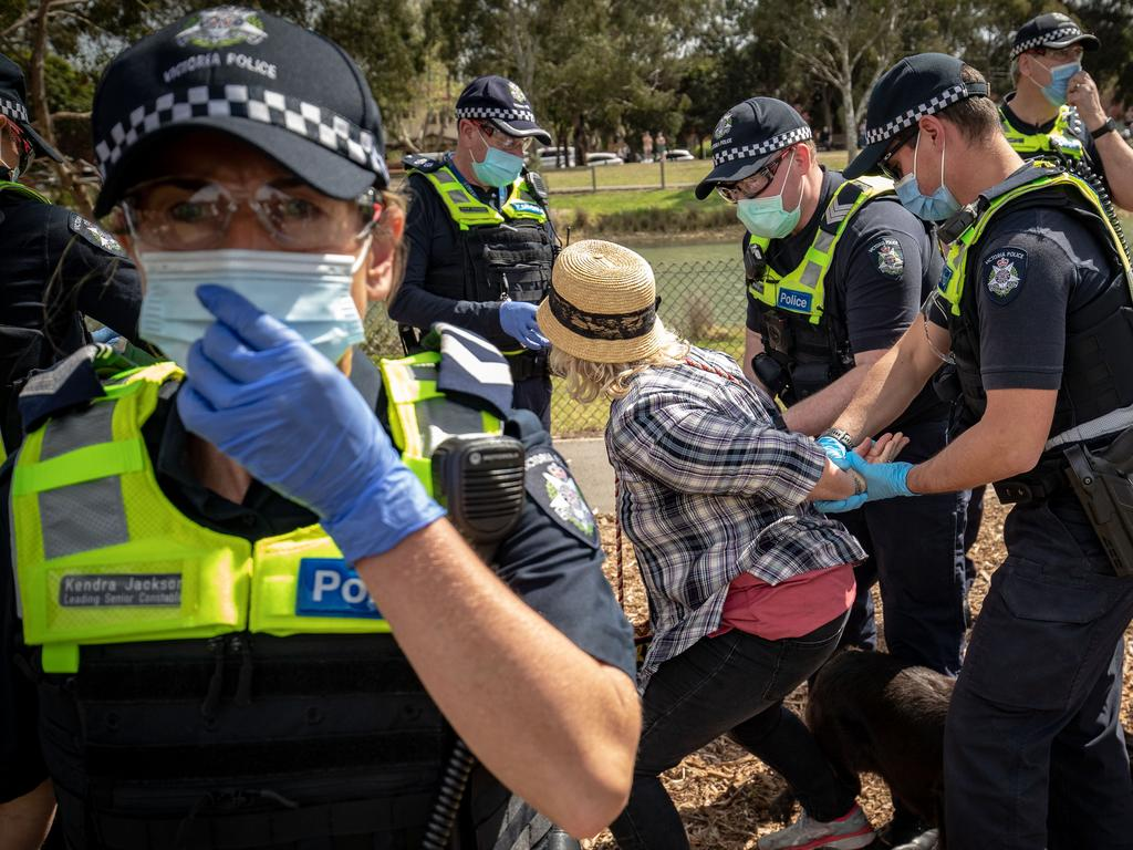 A woman is detained by police at Elsternwick Park on Saturday. Picture: Darrian Traynor/Getty Images