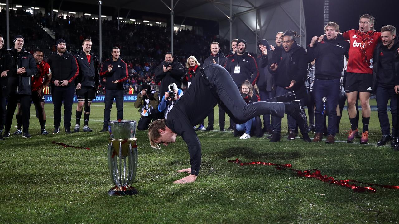 Crusaders coach Scott Robertson dances alongside the Super Rugby trophy.