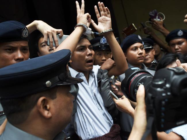 Myanmar journalist Kyaw Soe Oo is escorted by police after being sentenced by a court to seven years in jail in Yangon on September 3, 2018. Picture: AFP