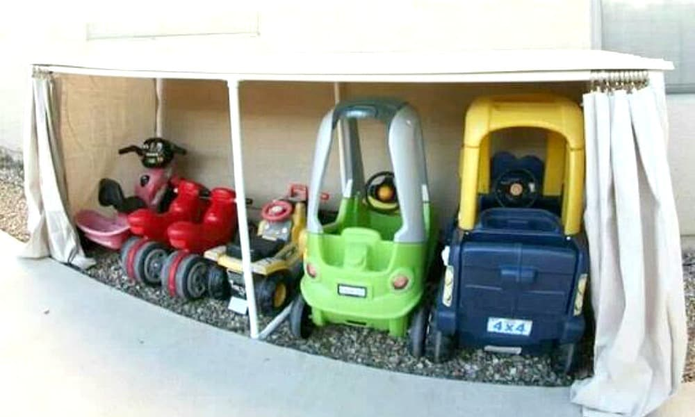 COVERED KIDDIE GARAGE - Take no notice of those fancy cubby houses with carports doing the rounds on the internet. This hack using a cheap table and shower curtain and turns them into the perfect solution to store your kids' outdoor wheelie what-have-yous in the one spot and out of the rain. Image: Spaceships and Laser Beams / Via Pinterest