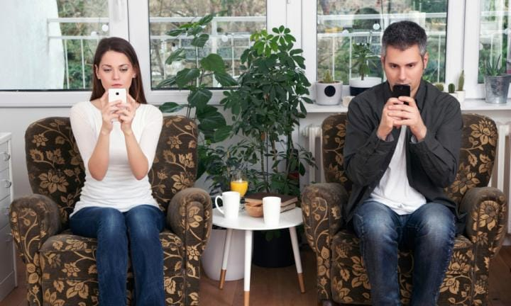 Young couple addicted to their smartphones