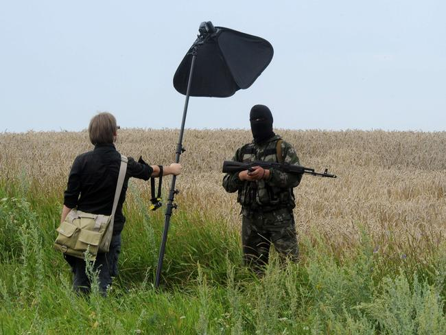 A masked armed separatist militant poses for a photographer near the site of the crash of a Malaysia Airlines crash. Picture: AFP/Dominique Faget