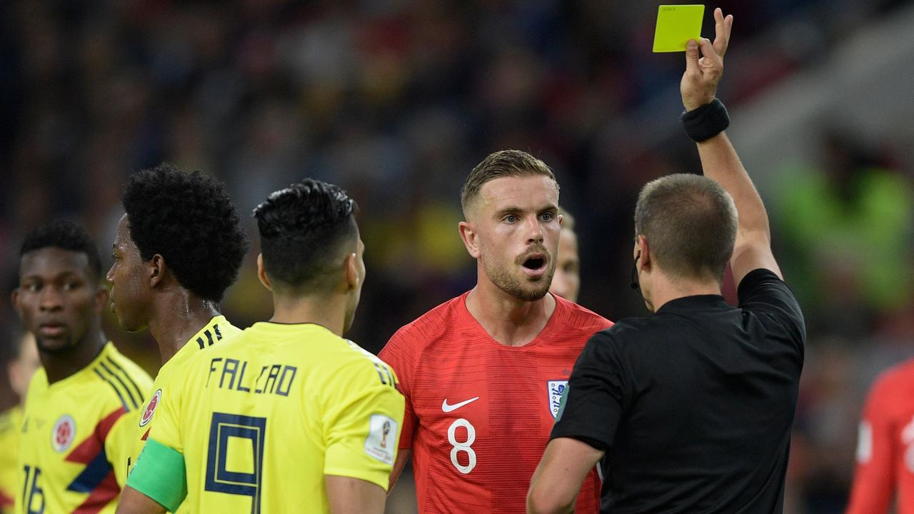England's midfielder Jordan Henderson is handed a yellow card against Colombia.