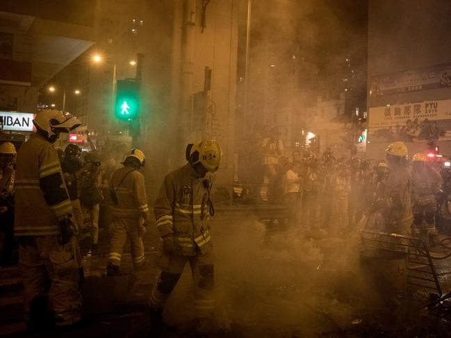 Firemen extinguish a burning barricade lit by pro-democracy protesters during a protest gathering in front of Mong Kok police station. Picture: Getty