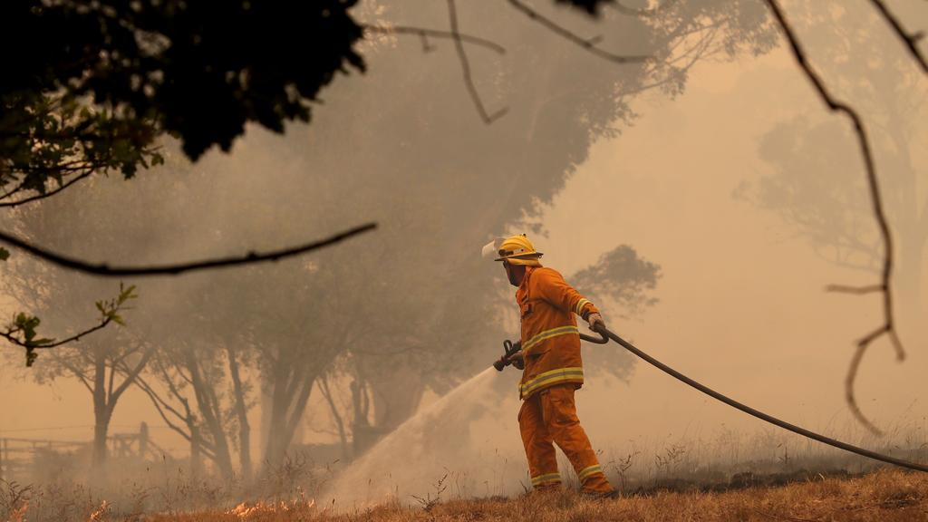 A CFS firefighter battles a fire as it runs across a paddock near a home on Ridge Road at Woodside in the Adelaide Hills on December 20, 2019. AAP Image/Kelly Barnes.