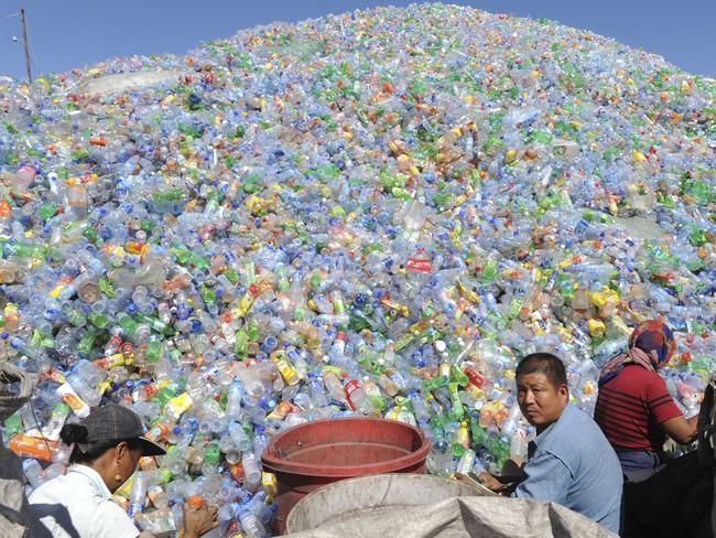 Workers sort recyclable plastic bottles at a bottle recycling site in Shenyang in northeast China's Liaoning province. Picture: AP Photo
