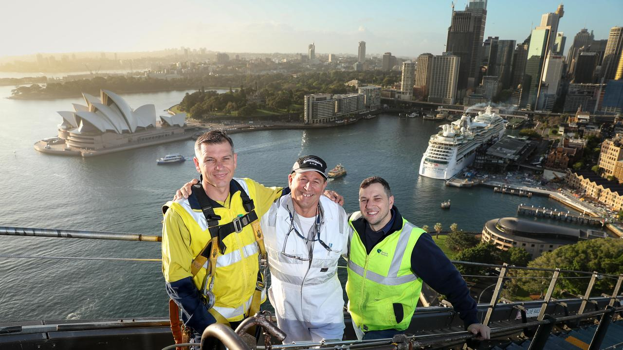 Mirko Cerovac (white overalls) with his sons Joseph and Goran (in the harness) have been maintaining the Sydney Harbour Bridge together for many years. Picture: Ryan Osland