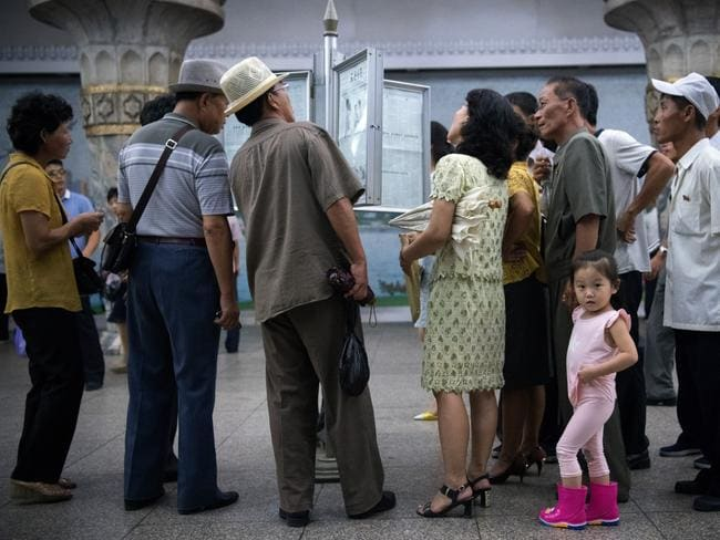 North Korean locals read a newpaper displayed at a train station, while a little girl looks directly at Carl's camera. Picture: Carl Court/Getty Images