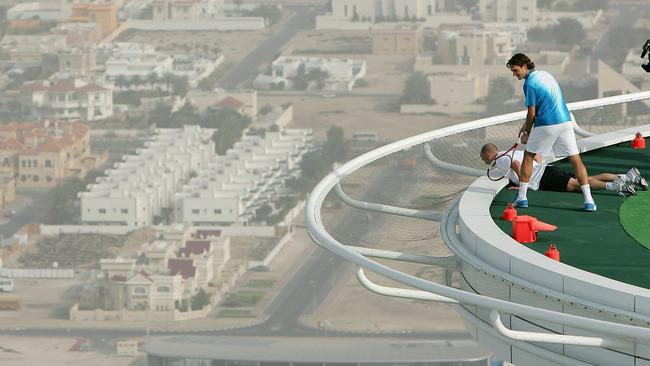 Federer and Agassi looking for ball over side of court on helipad of Burj Al Arab hotel in Dubai.