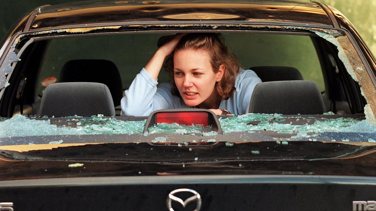 Sydney resident Claire Reynolds inspects her destroyed car windscreen following a freak hailstorm in 1999.