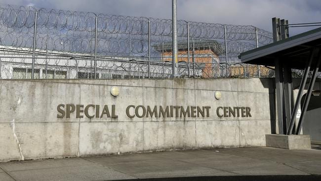 A sign for McNeil Island Special Commitment Centre next to a fence lined with razor wire. Picture: Ted Warren